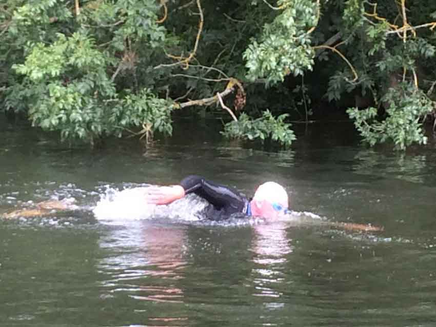 a man swimming near the river edge