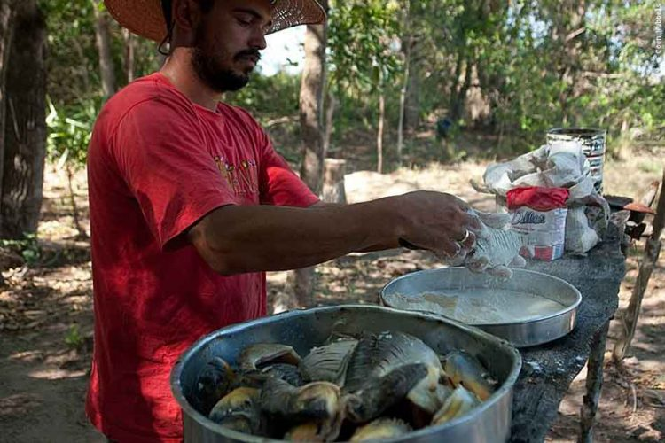 a man cooking piranha by river